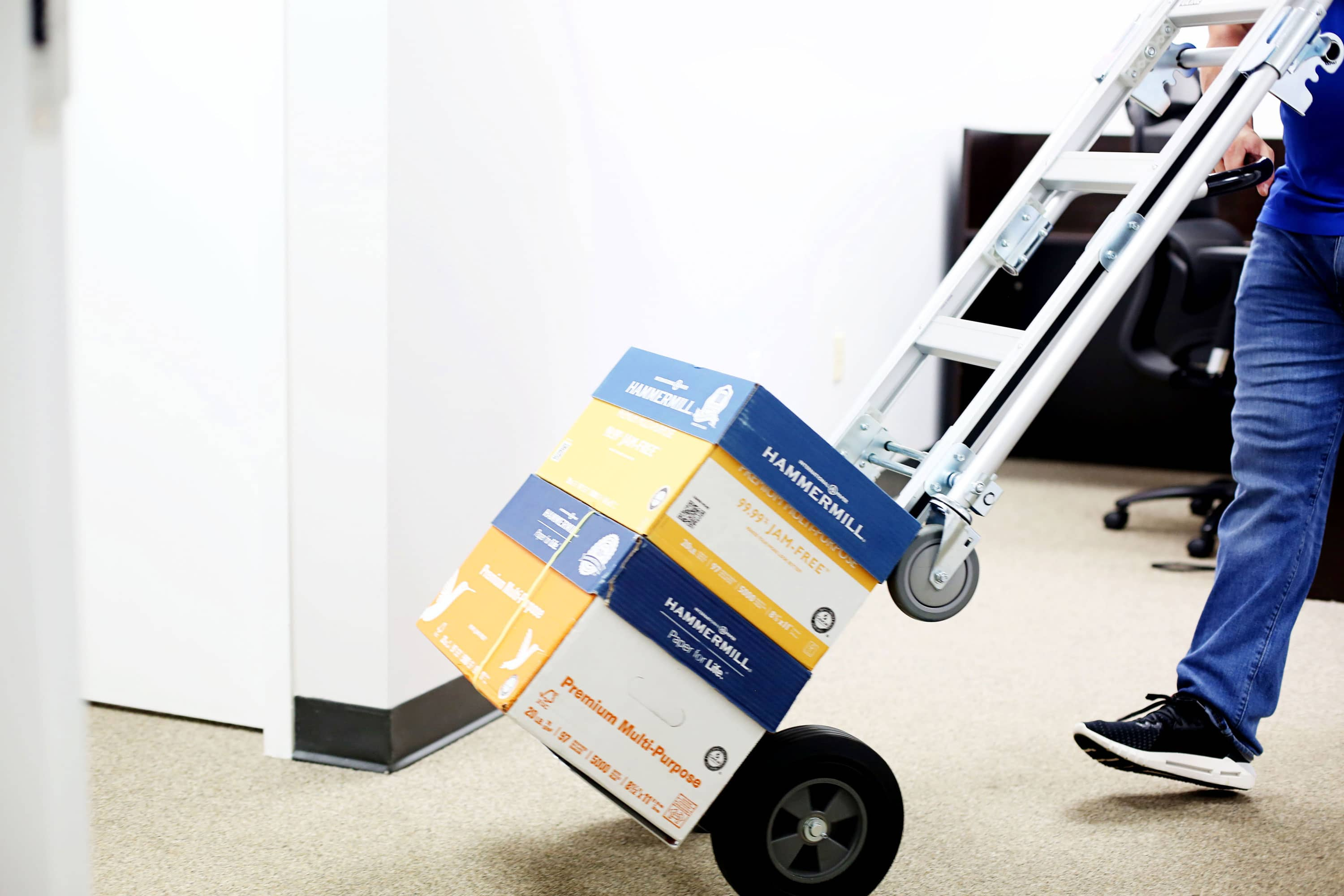 Expedite Delivery System Employee With Dolly Truck Stacked with Paper Boxes