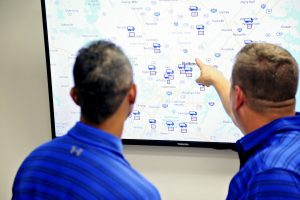 Expedite Delivery Service Employees Looking At Digital Map